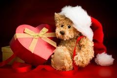 Плюшевый медвежонок нося шляпу рождества и обнимая коробку Стоковая Фотография RF