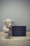Плюшевый медвежонок сидит на деревянных полах Стоковое Изображение