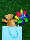 Плюшевый медвежонок с игрушкой ветра в хозяйственной сумке Стоковое фото RF