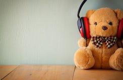 Плюшевый медвежонок с наушниками над деревянным столом Стоковое фото RF