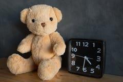 Плюшевый медвежонок с часами, плюшевый медвежонок сидя на деревянном поле против Стоковые Фото