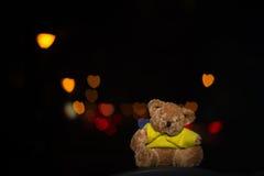 Плюшевый медвежонок с bokeh сердца на черной предпосылке Стоковое Изображение