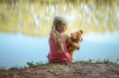 Плюшевый медвежонок ухода маленького ребенка пока сидящ совместно задний взгляд Стоковые Фото