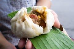 Плюшка свинины китайская в руке Стоковое Изображение