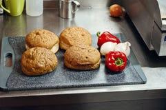 Плюшки гамбургера на разделочной доске Стоковые Изображения