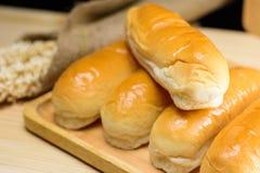 Плюшки горячей сосиски в деревянной плите на деревянном столе Стоковые Фото