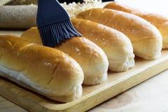 Плюшки горячей сосиски в деревянной плите на деревянном столе Стоковая Фотография RF