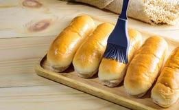 Плюшки горячей сосиски в деревянной плите на деревянном столе Стоковое Изображение RF