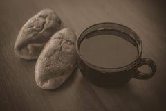 2 плюшки и большой чашка чаю на деревянном столе в винтажном тоне Стоковое Изображение RF