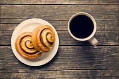 Плюшки и кофе циннамона Стоковые Изображения