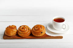 Плюшки и чашка чаю изюминки на белой таблице Стоковые Изображения RF