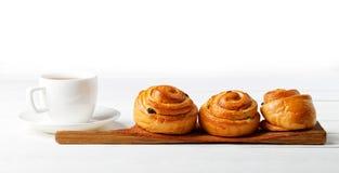 Плюшки и чашка чаю изюминки на белой таблице Стоковое Фото