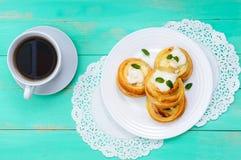 Плюшки свеже испеченные, творог, с сливк и листьями и чашкой чаю мяты на белой плите Стоковые Фотографии RF
