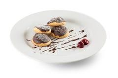 Плюшки с замороженностью шоколада на белой плите изолированной на белом b Стоковые Изображения
