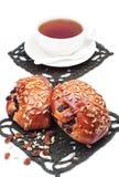 2 плюшки с изюминками и семенами подсолнуха и чашкой чаю Стоковое фото RF