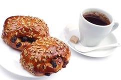 2 плюшки с изюминками и семенами подсолнуха с кофе Стоковые Изображения