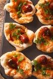 Плюшки с крупным планом сосиски, сыра и лука в блюде выпечки Vert Стоковое Изображение RF