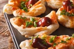 Плюшки слойки с макросом сосиски, сыра и лука в блюде выпечки H Стоковая Фотография
