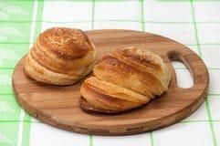 Плюшки с семенами сезама на доске кухни деревянной Стоковые Фотографии RF