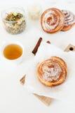 Плюшки травяного чая и помадки с сахаром и циннамоном на белой предпосылке Стоковое Фото