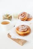 Плюшки травяного чая и помадки с сахаром и циннамоном на белой предпосылке Стоковое Изображение