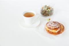 Плюшки травяного чая и помадки с сахаром и циннамоном на белой предпосылке Стоковые Изображения RF