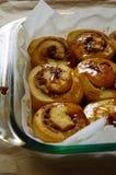 Плюшки циннамона заморосили с карамелькой в стеклянном блюде выпечки Стоковое Изображение
