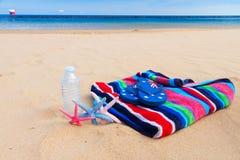 Пляжный полотенце и бутылка воды на песчаном пляже Стоковое Изображение