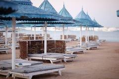 Пляж вечера с парасолями и loungers солнца на пляже Стоковое Изображение
