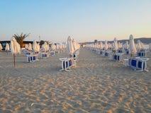 Пляж в восходе солнца с шезлонгами и зонтиками стоковые изображения rf