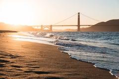 Пляж и золотой строб на заходе солнца Стоковые Изображения