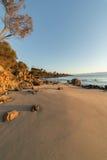 Пляж и утесы во время захода солнца Стоковое Изображение RF