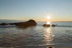 Пляж и утесы во время захода солнца Стоковое фото RF