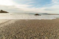 Пляж и утесы во время захода солнца Стоковые Изображения