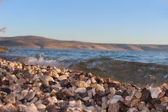 Пляж, камни камешка и волна стоковые изображения rf