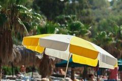 Пляж моря зонтика, люди лежа на loungers солнца Стоковые Изображения