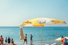 Пляж моря зонтика, люди лежа на loungers солнца Стоковое Фото