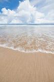 Пляж песка волн и день облаков солнечный Стоковые Фотографии RF