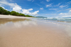 Пляж песка волн и день облаков солнечный Стоковые Изображения