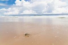 Пляж песка волн и день облаков солнечный Стоковая Фотография