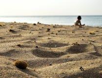 Пляж песка с сидя женщиной в предпосылке Стоковое Изображение RF