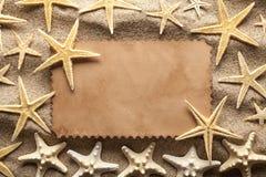 Пляж предпосылки - бумажная карточка и морские звёзды Стоковое Изображение