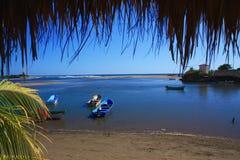 Пляж рыбацкого поселка, малая вода на заходе солнца Стоковые Фотографии RF