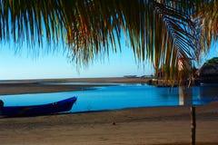 Пляж рыбацкого поселка, малая вода на заходе солнца Стоковая Фотография RF