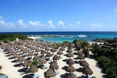 Пляж с зонтиками и голубым морем Стоковые Изображения RF