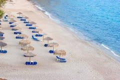 Пляж с зонтиками солнца и sunbeds Стоковая Фотография