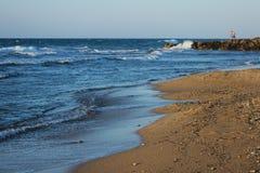 Пляж с морем развевает конец-вверх в летнем времени Крит Греция приземлился продолжающееся солнце лучей плоскости Стоковое Фото