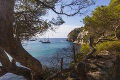 Пляж увиденный среди деревьев на солнечном утре, Minorca Macarella Стоковые Изображения