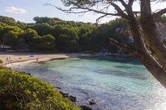Пляж увиденный среди деревьев на солнечном утре, Minorca Macarella Стоковая Фотография