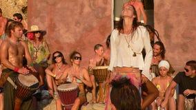 Пляж Benirras, Ibiza, Испания - 23-ье июля 2006: Серии людей наблюдая заход солнца пока играющ барабанчики и другие аппаратуры Стоковые Изображения RF